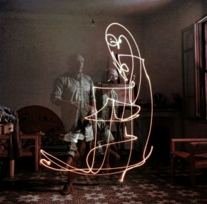 Triple exposure of artist Pablo Picasso drawing w. light at his home in Vallauris.