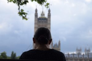 Comical photograph of woman sat in front of the houses of parliament