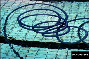 Photograph of blue hose in blue swimming pool by Ferdinando Scianna
