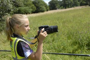 Girl taking a photograph on a photography course at Hatchlands Park