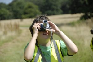 child taking a photograph at a photography workshop at Hatchlands Park