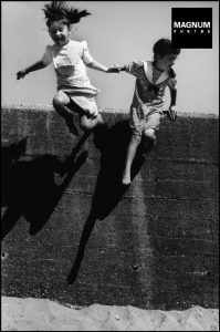 Martine Franck black and white photograph of children jumping off a wall