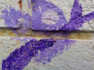 Close up photograph of colourful paint on a wall at a school