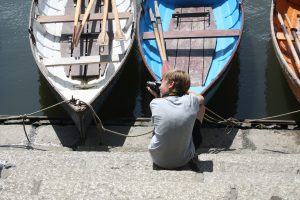 Teen photographing the boats on the river thames