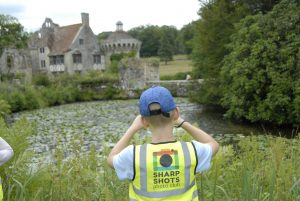 Boy photographing Scotney Castle on kids photography course in Kent