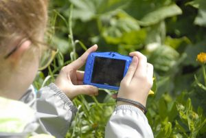 child taking a photo of a flower on a photography course at Tatton Park
