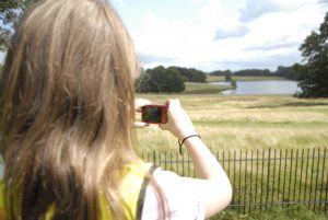 Girl photographing the beautiful landscapes at Tatton Park