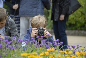 Child taking a photo of flowers at Waddesdon Manor on kids photography course