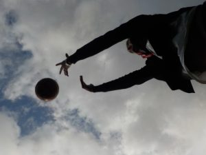 low perspective photograph of woman throwing a ball