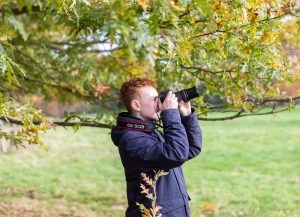 Teen taking photographs of leaves at Hatchlands Park in Autumn