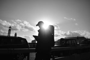 Black and white photograph taken on London bridge by teenager of a man and cars silhouetted against the sun